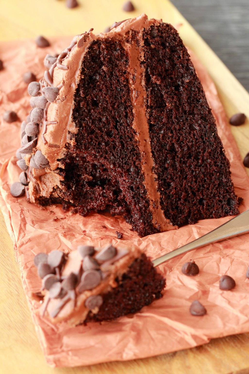 A slice of chocolate cake lying on some brown tissue paper, with a forkful of cake next to it.