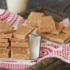 Squares of vegan fudge stacked up on white plates.