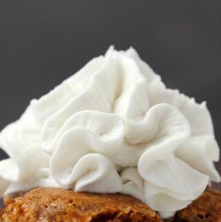 Vegan whipped cream on top of a slice of apple cake.