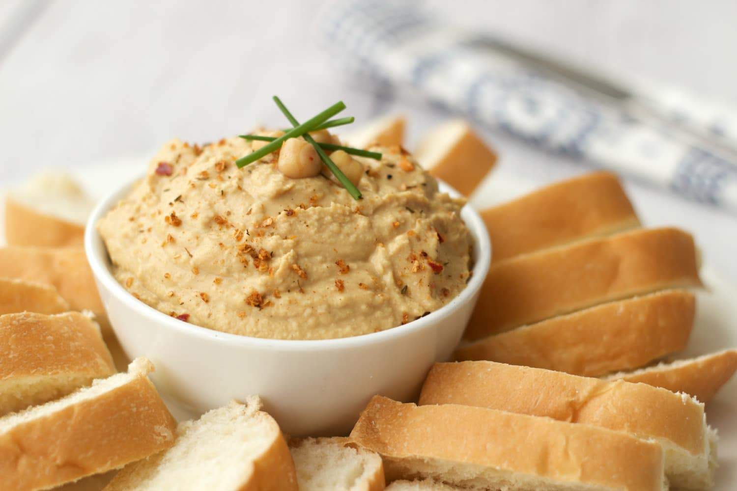 Spicy vegan hummus in a white bowl surrounded by sliced bread.