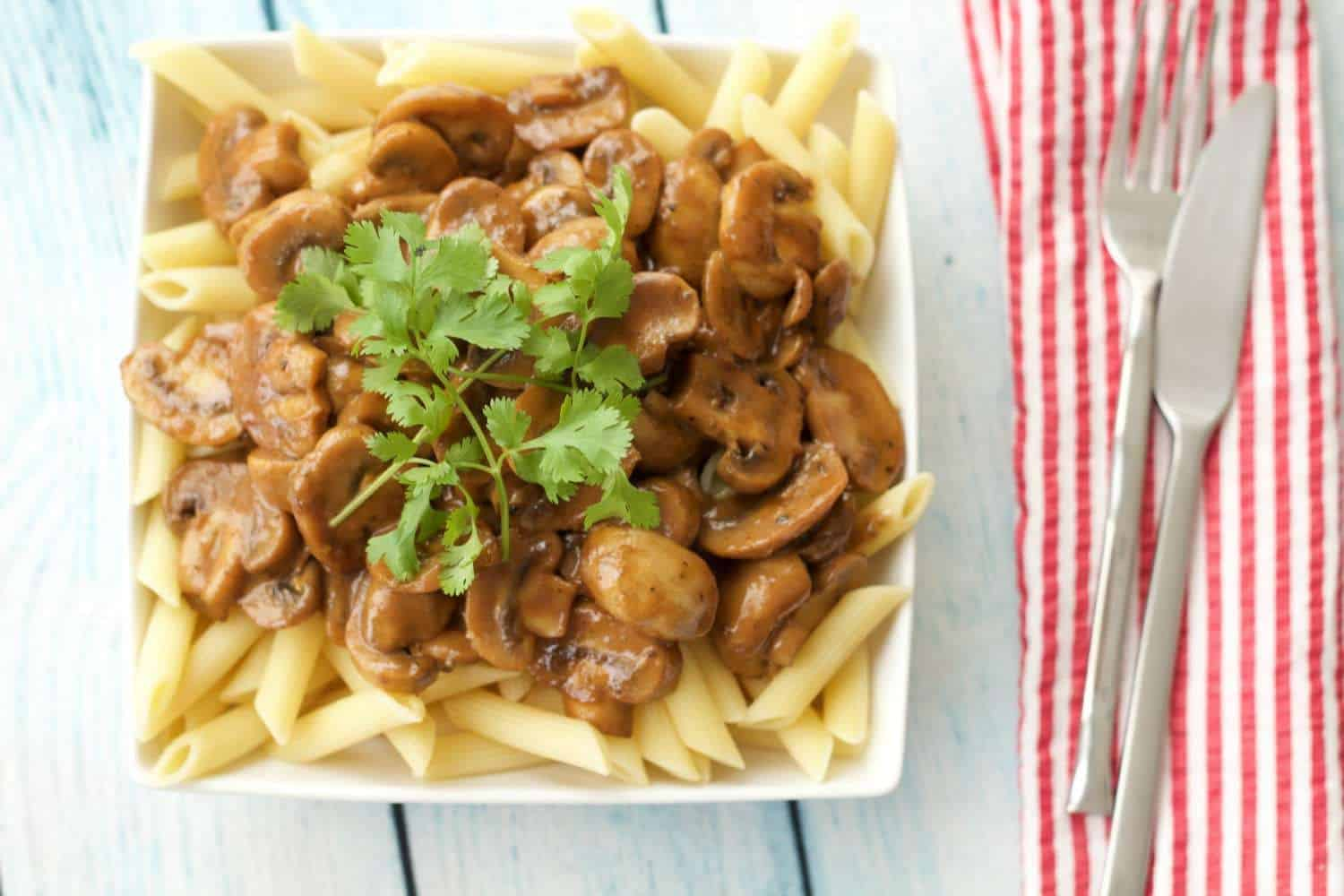 Tahini mushroom sauce over penne in a square white bowl.