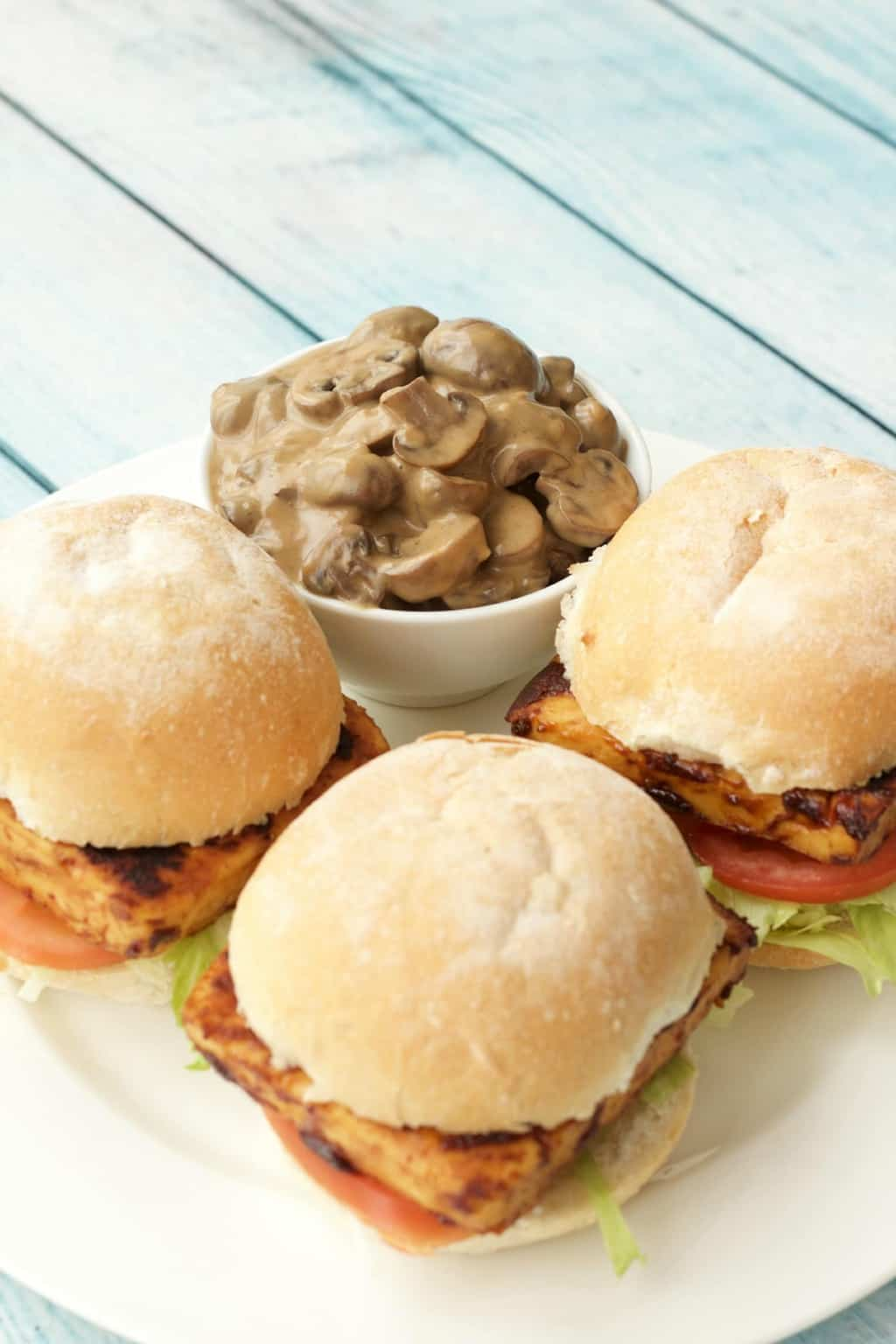 Three tofu burgers and a bowl of mushroom sauce on a white plate.