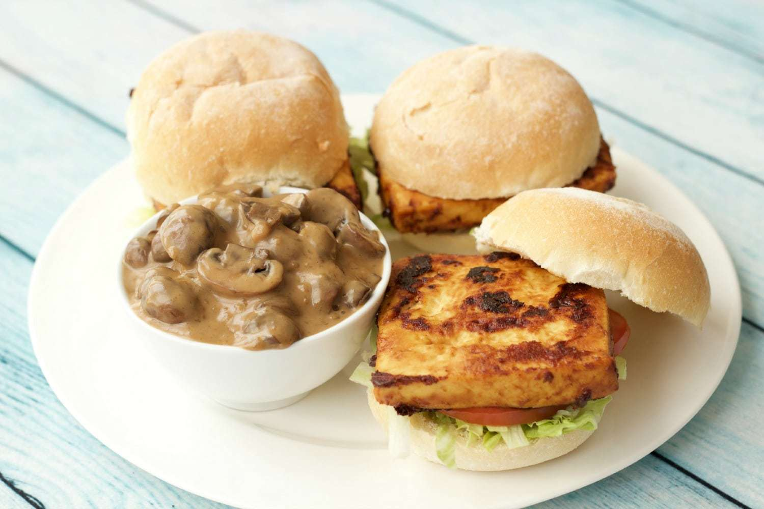 Three vegan tofu burgers and a bowl of mushroom sauce on a white plate.