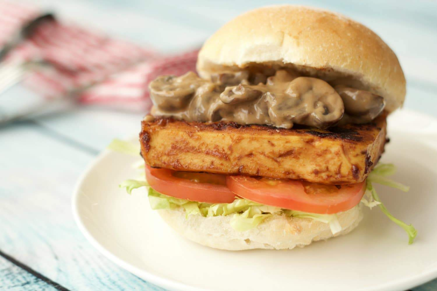 Tofu Burger with mushroom sauce on a white plate with a red and white napkin in the background.