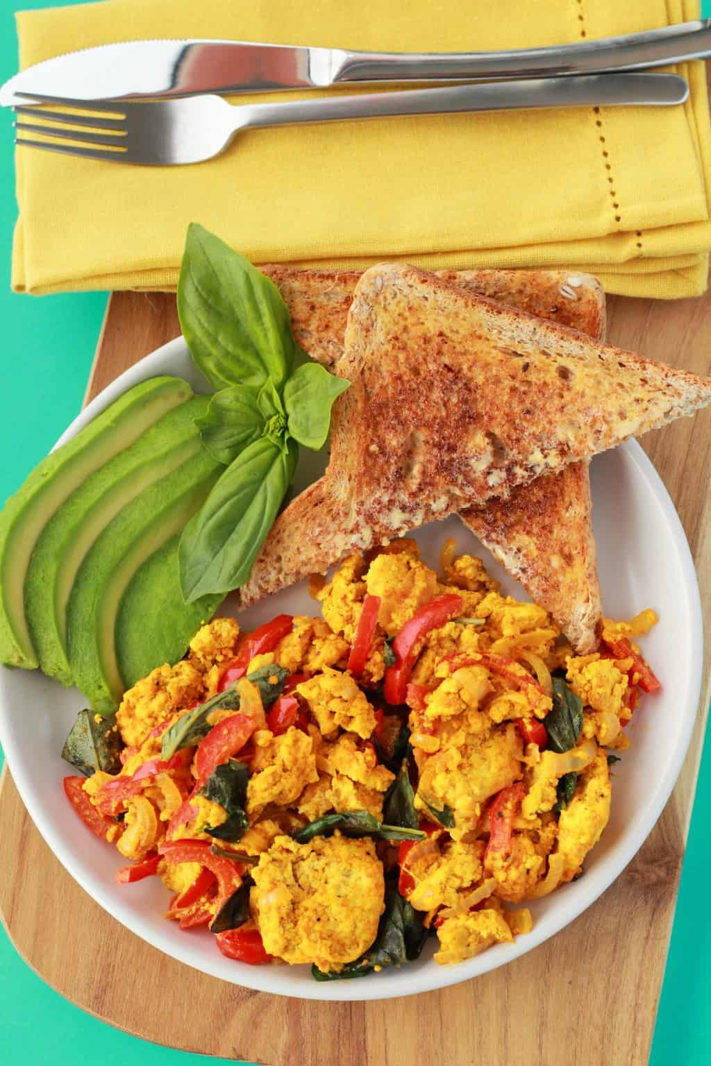 Tofu Scramble on a white plate with toast triangles, fresh basil and sliced avocado, a yellow napkin and cutlery in the background.