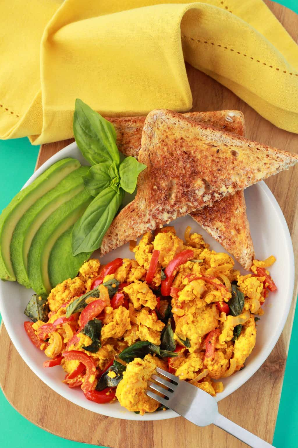 Tofu Scramble on a white plate with toast triangles, fresh basil and sliced avocado, a yellow napkin in the background.