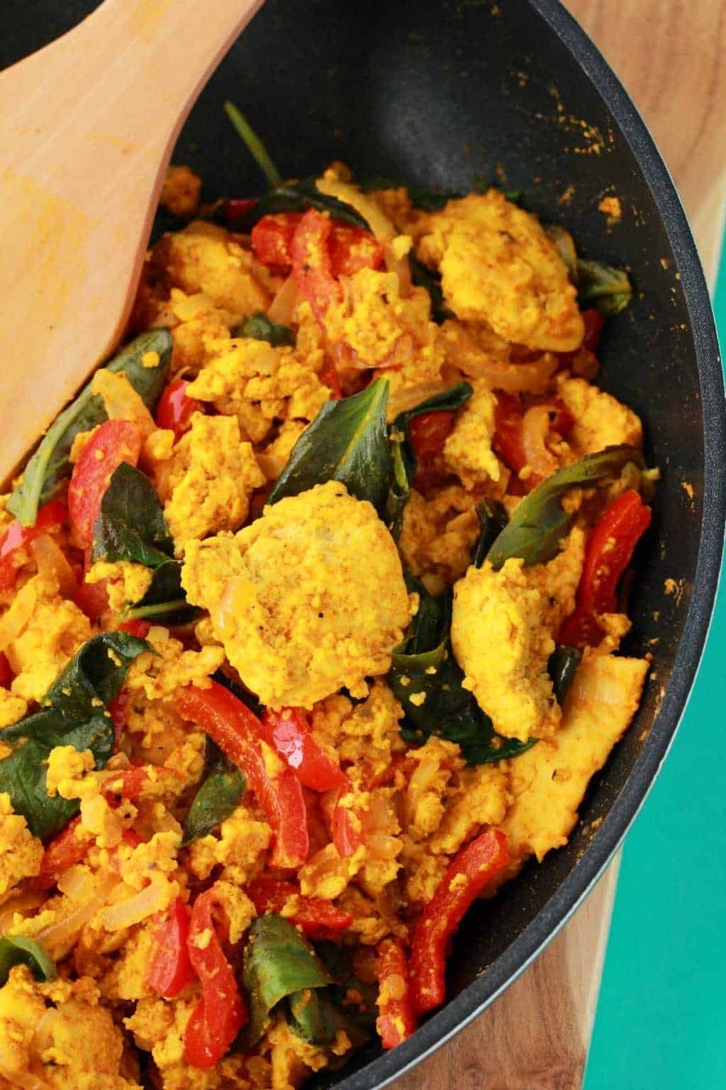Tofu Scramble in a frying pan with a wooden spoon.