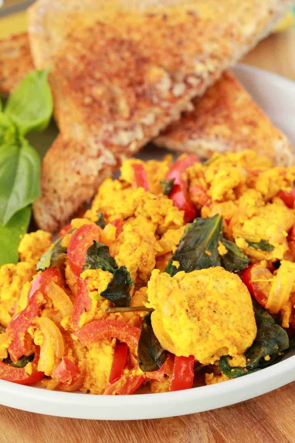 Tofu Scramble on a white plate with toast triangles and fresh basil.