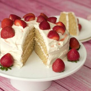 Vegan vanilla cake on a white cake stand.