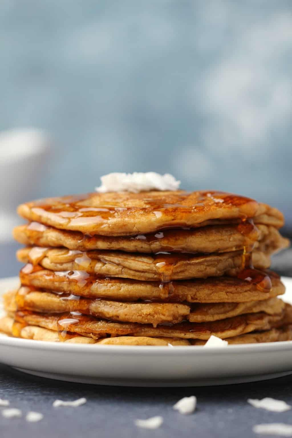 Vegan coconut pancakes topped with coconut flakes and syrup on a white plate.