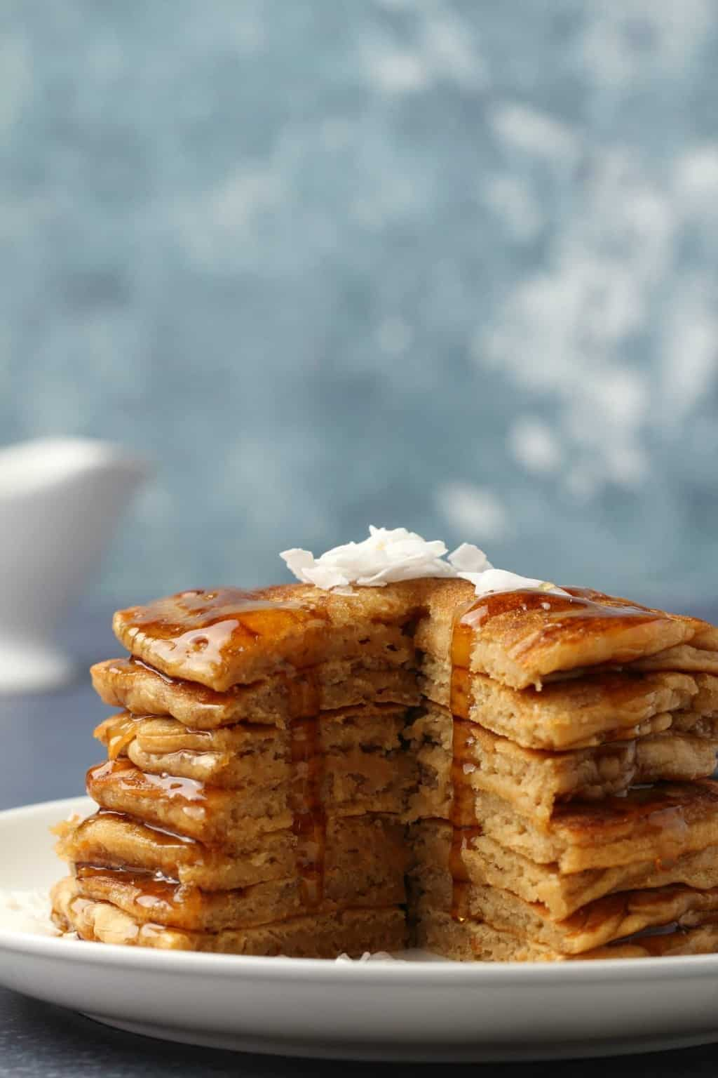 A stack of vegan coconut pancakes on a white plate.