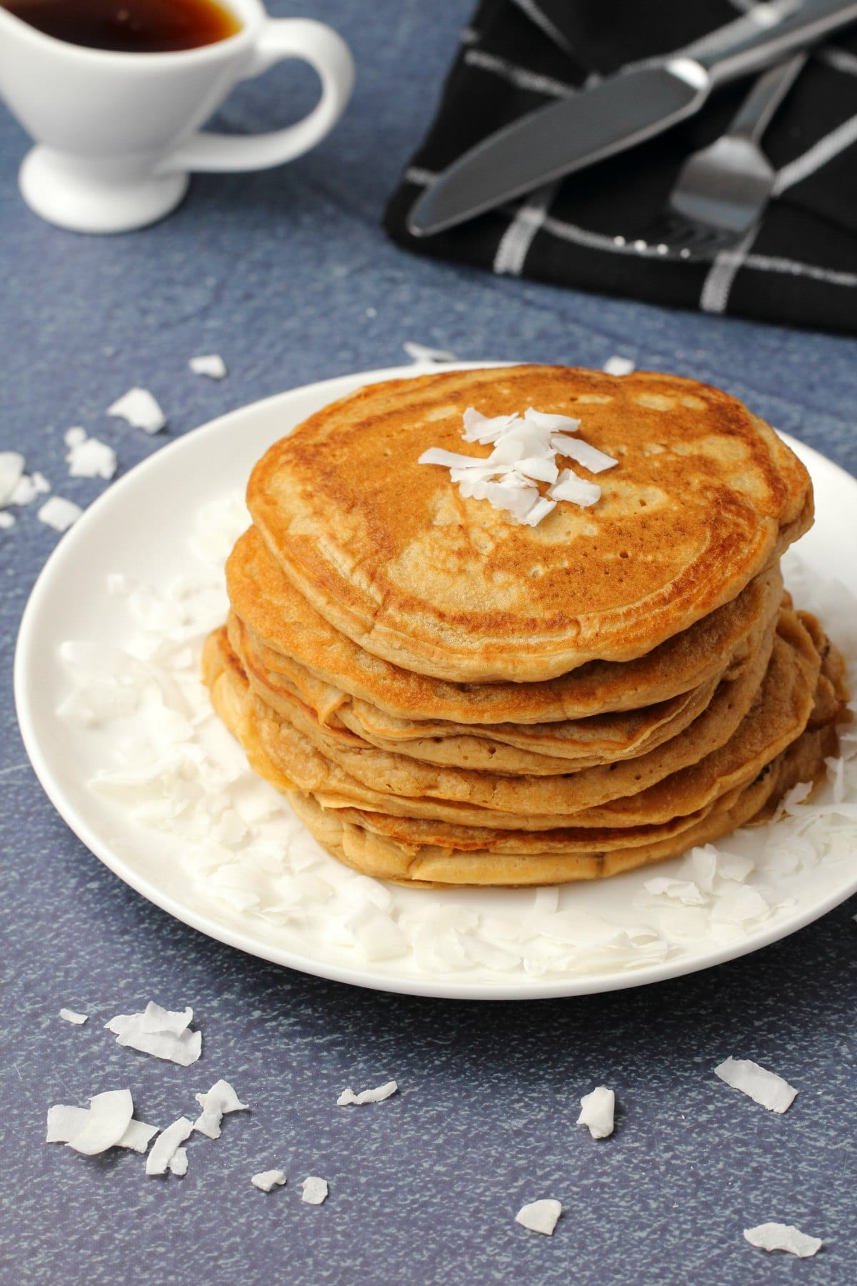 Vegan coconut pancakes topped with coconut flakes and stacked up on a white plate.