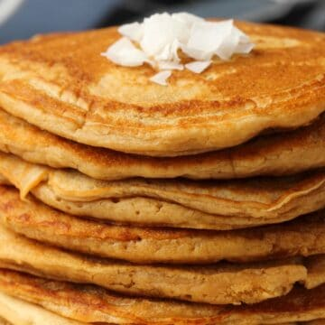 Vegan coconut pancakes stacked up on a white plate.