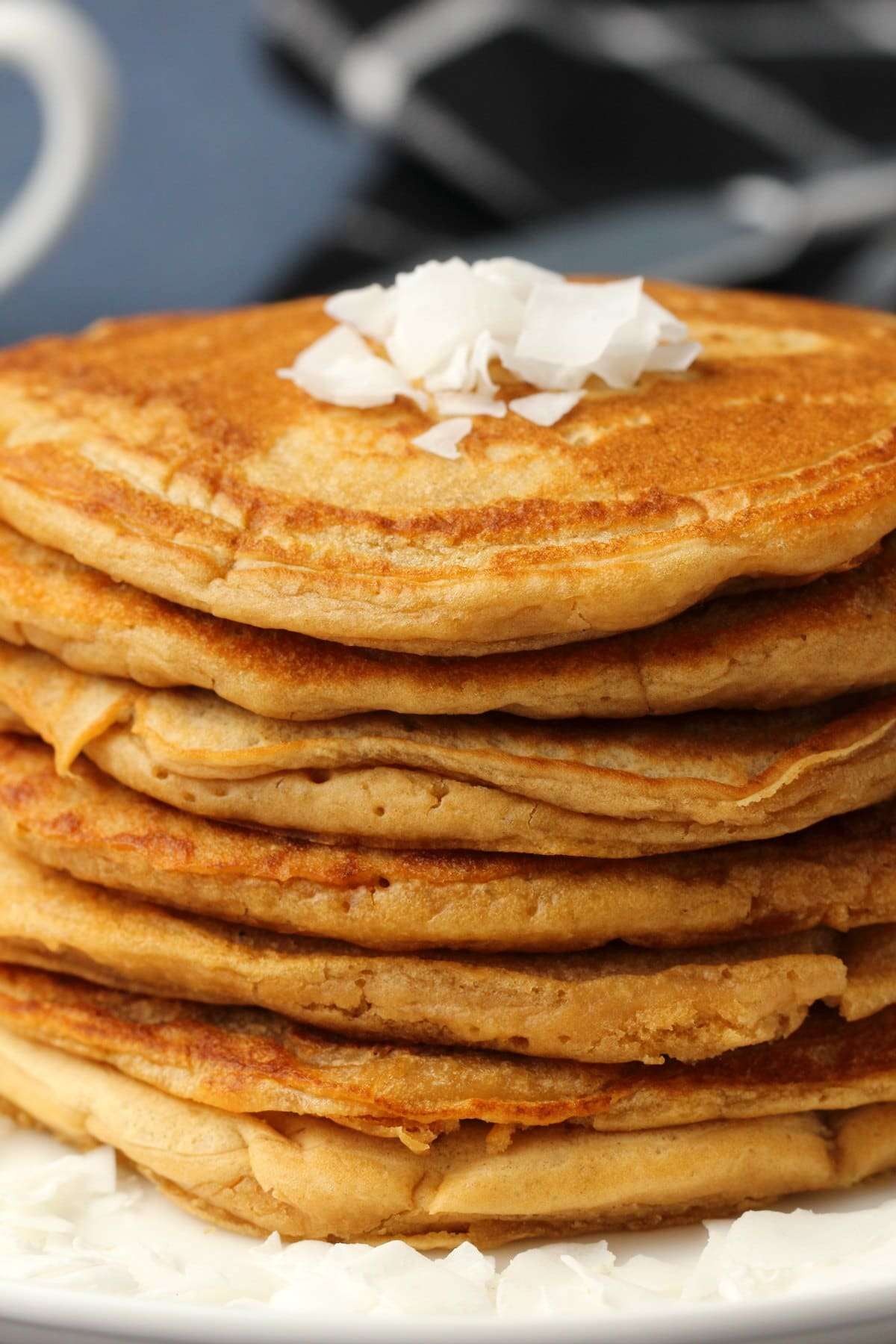 Vegan coconut pancakes in a stack on a white plate.
