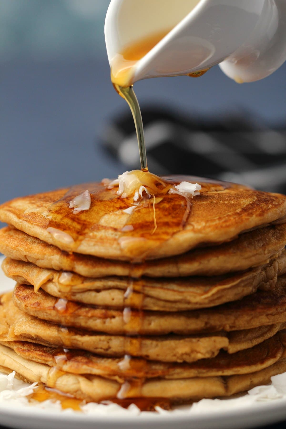 Syrup pouring over a stack of vegan coconut pancakes.