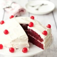 Red velvet cake topped with cherries on a white cake stand