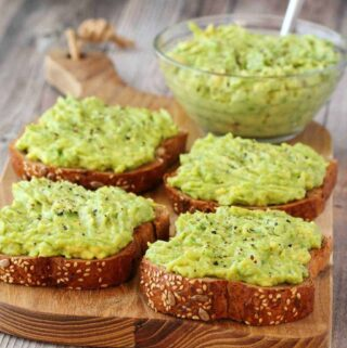 Slices of toast with avocado on a wooden board.