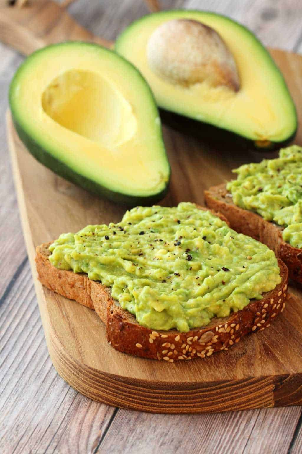 Avocado Toast topped with black pepper. Avocado halves in the background.