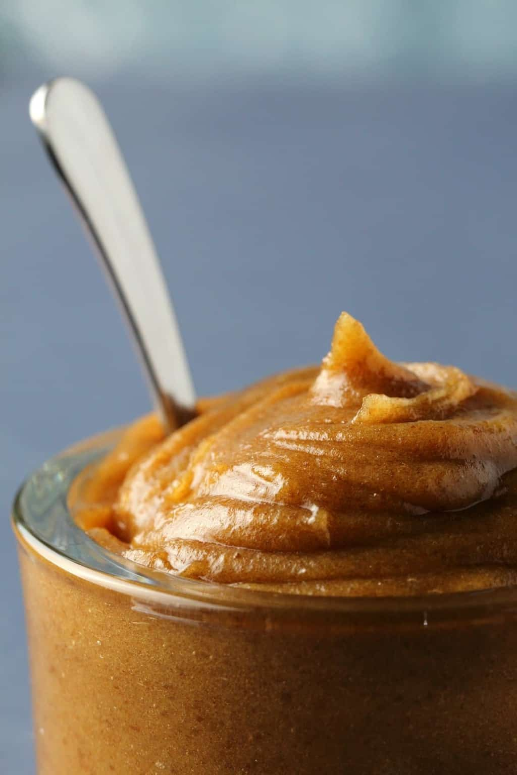 Date caramel in a glass jar with a spoon.