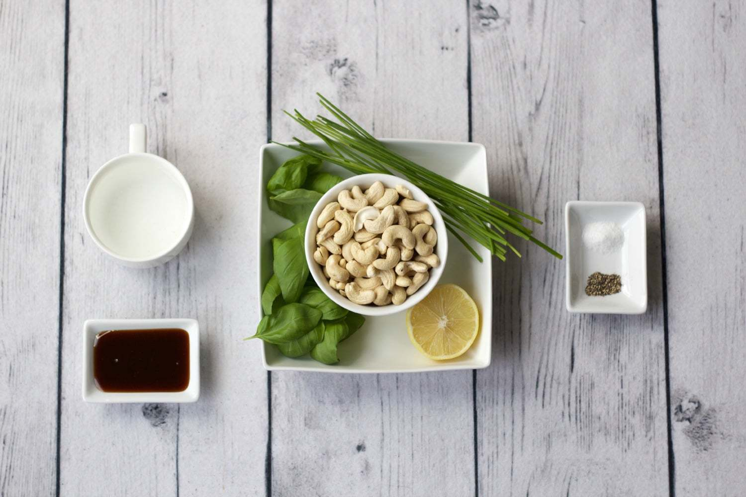 A bowl of cashews in a white bowl surrounded by basil leaves, chives and half a lemon on a white plate. A cup of water stands to the side, as does a small white plate with date syrup, and another small white plate with salt and other spice.