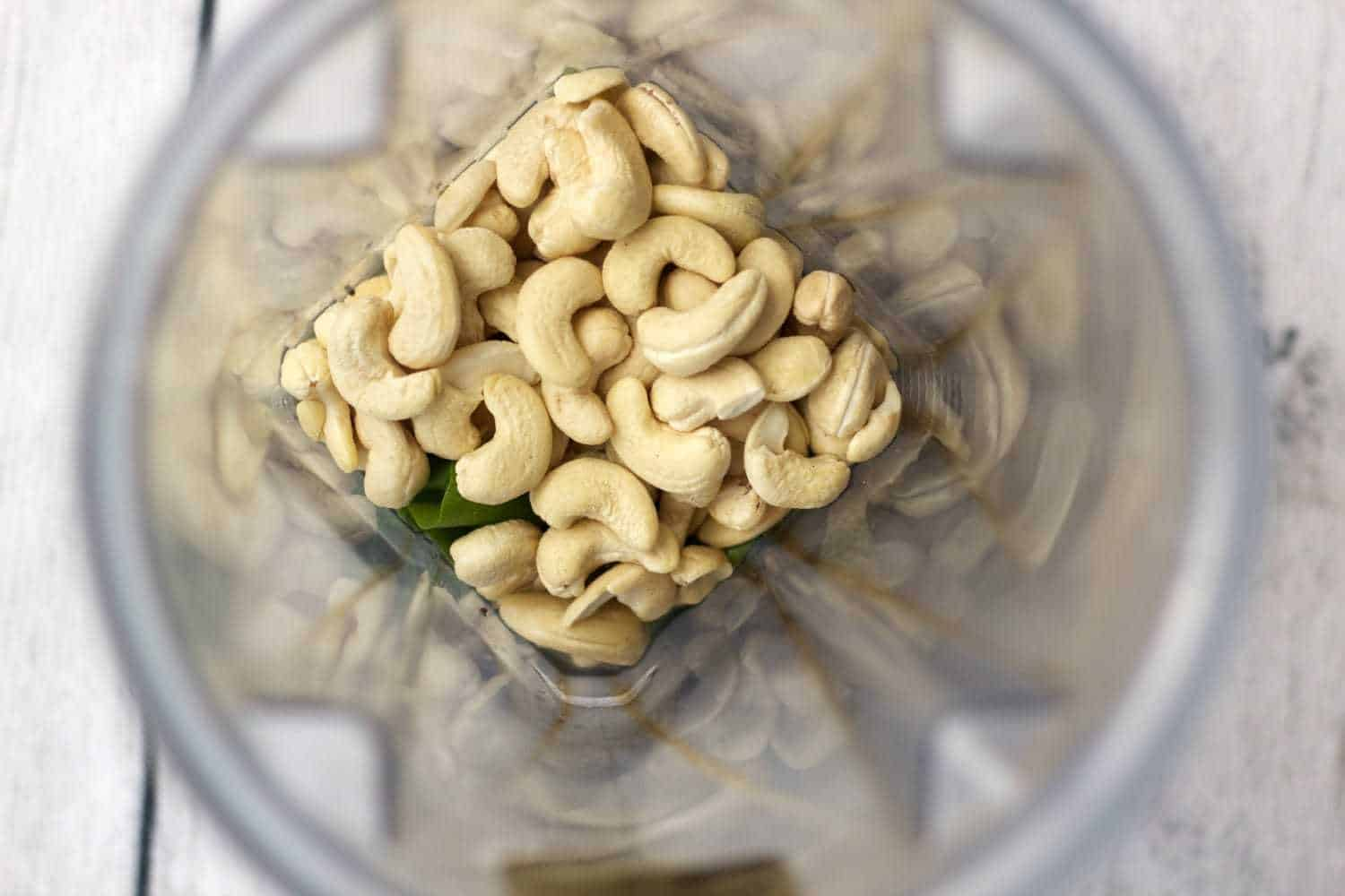 A blender jug with ingredients ready to blend. Cashew nuts can be seen at the top of the jug.