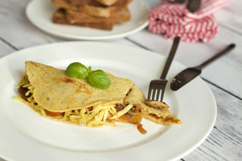 Light and fluffy Vegan Omelette served with vegan cheese, sauteed mushrooms, onion, tomato and vegan sausage. Breakfast of champions! #vegan #gluten-free #dairy-free #lovingitvegan