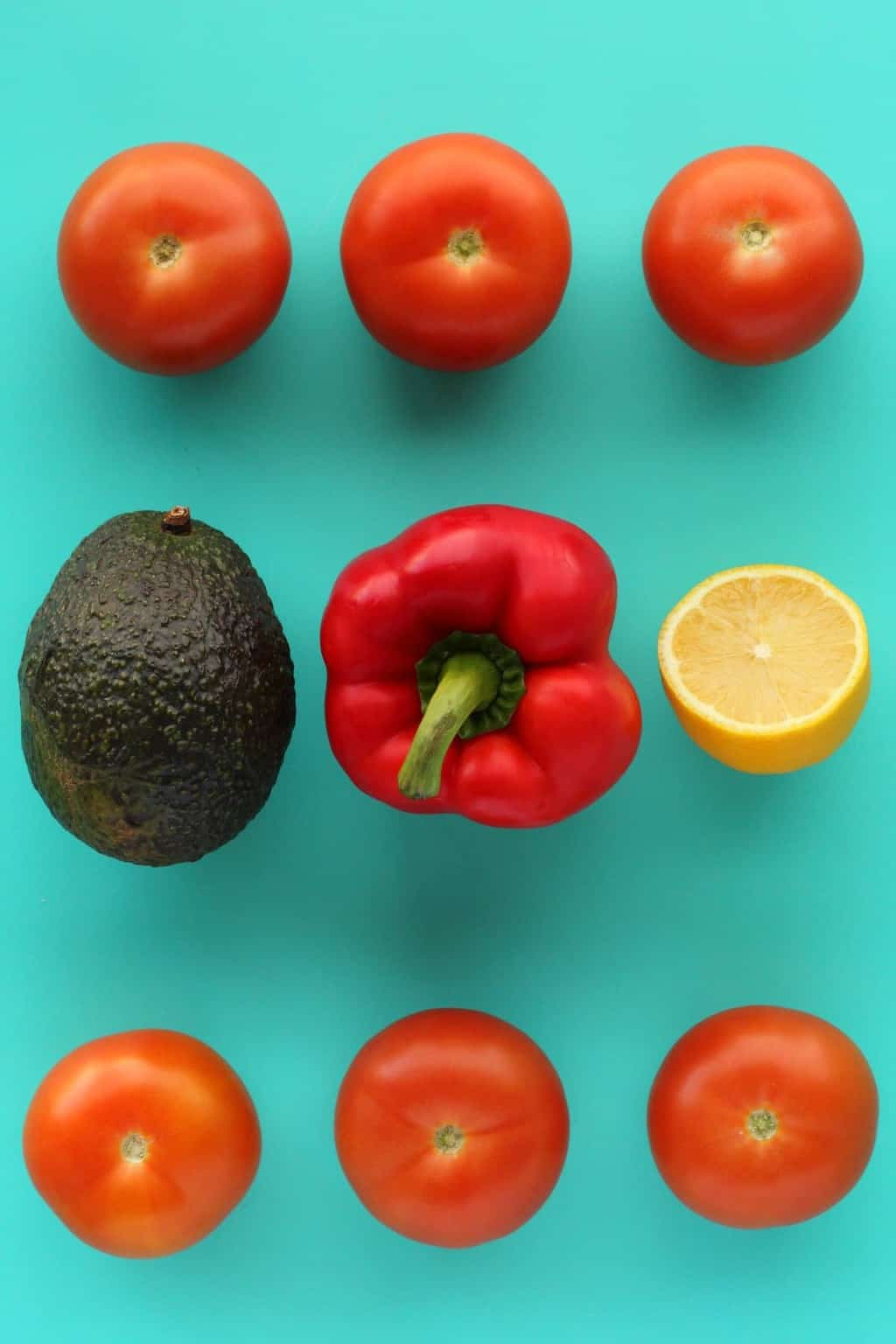Ingredients for a raw tomato soup, tomatoes, bell pepper, fresh lemon and avocado against a blue background.