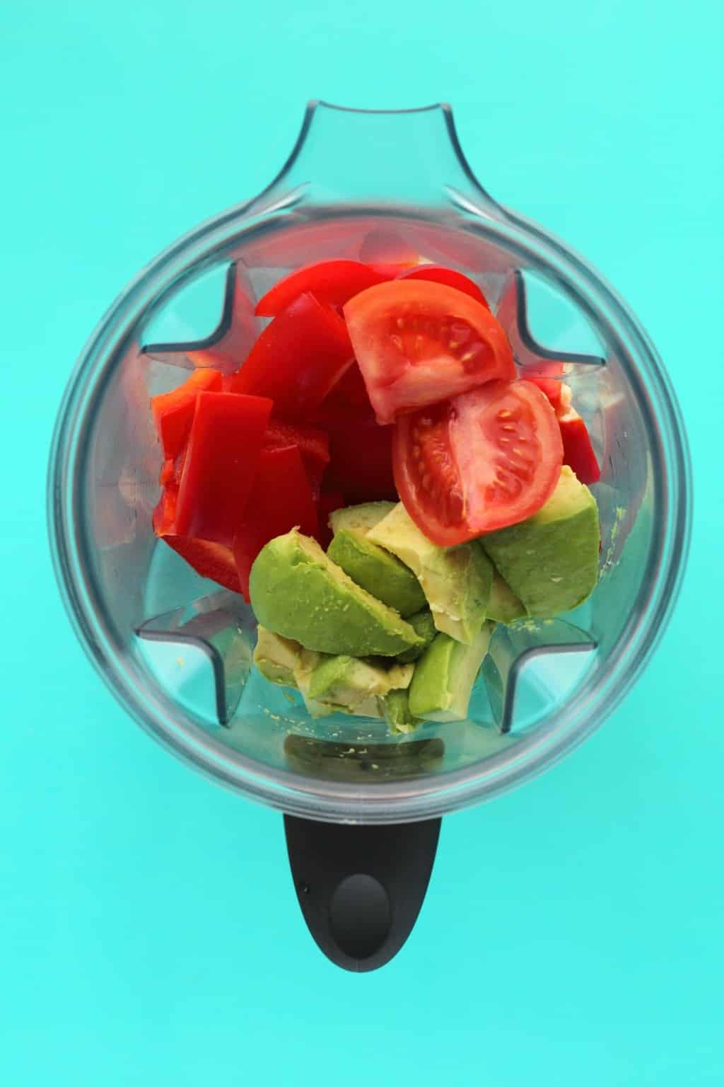 Ingredients for a raw tomato soup in a blender jug ready to be blended.