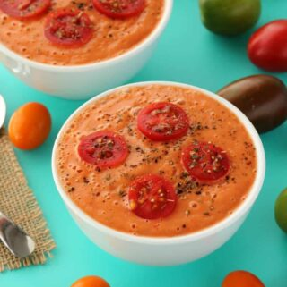Raw tomato soup in white bowls.