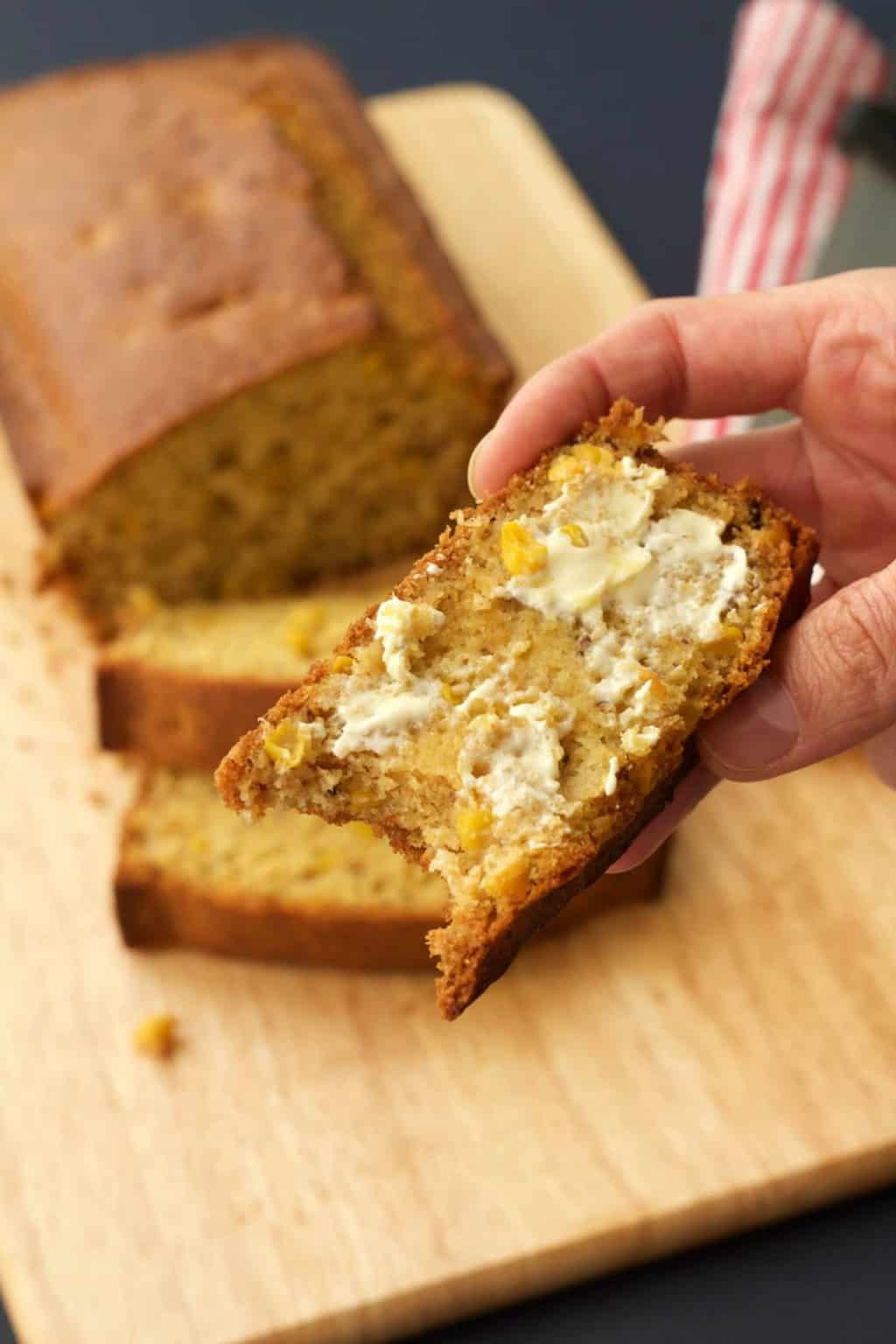A slice of buttered vegan cornbread with a bite taken out of it.