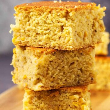 Vegan cornbread stacked up on a wooden board.