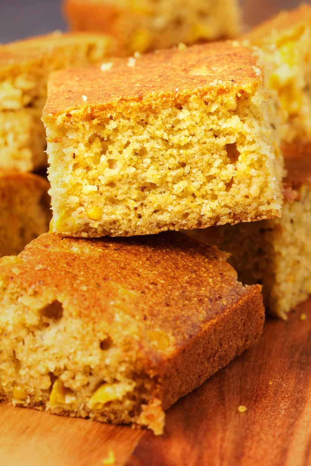 Vegan cornbread squares on a wooden board.