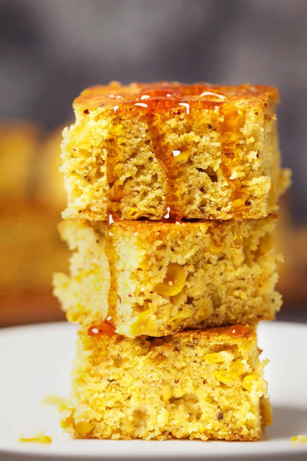 A stack of vegan cornbread drizzled with syrup.