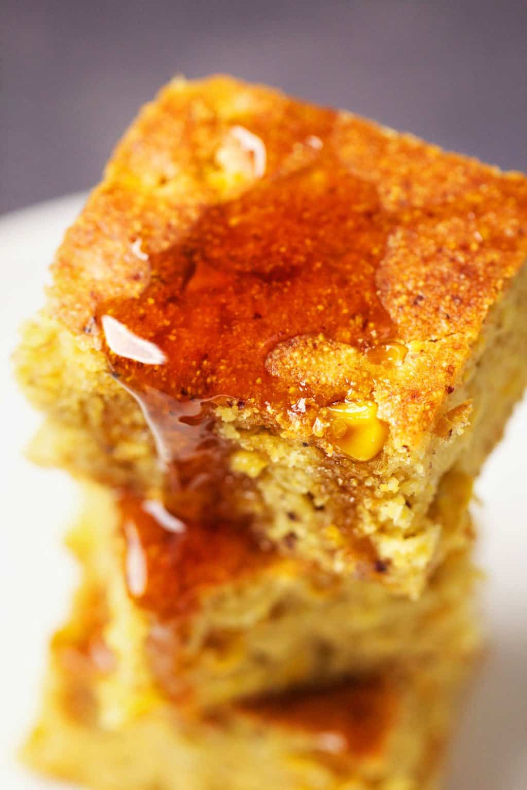 A stack of vegan cornbread with syrup on top.