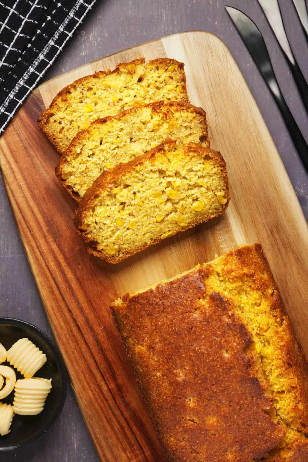 A loaf of vegan cornbread on a wooden board.