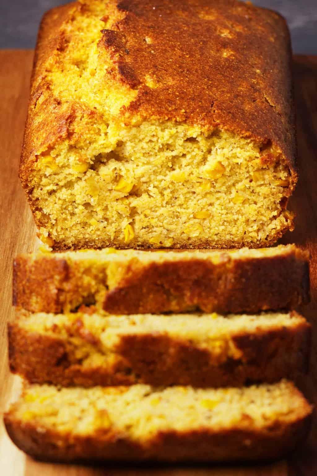 A loaf of vegan cornbread on a wooden board.