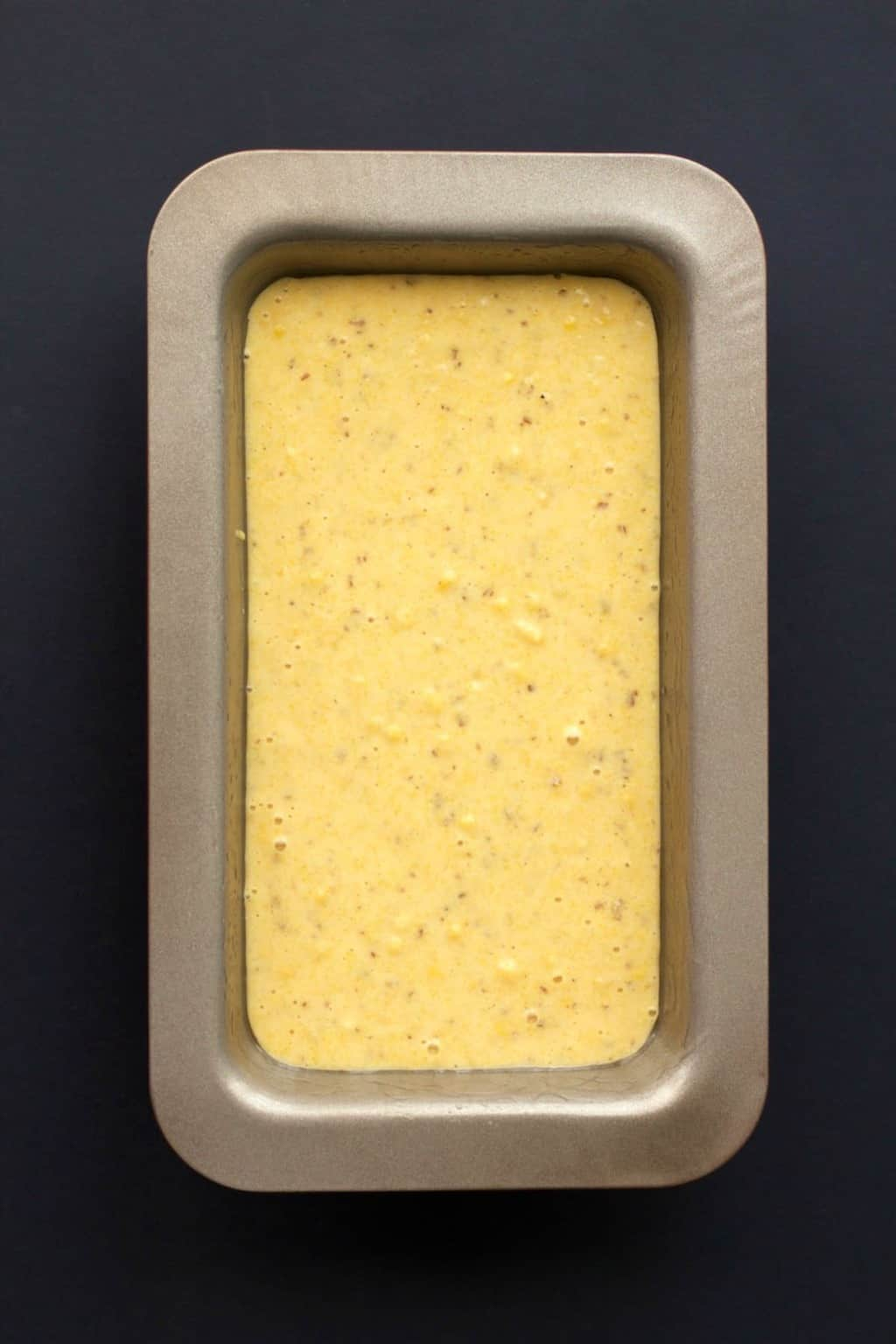Vegan cornbread batter in a loaf pan ready to go into the oven.