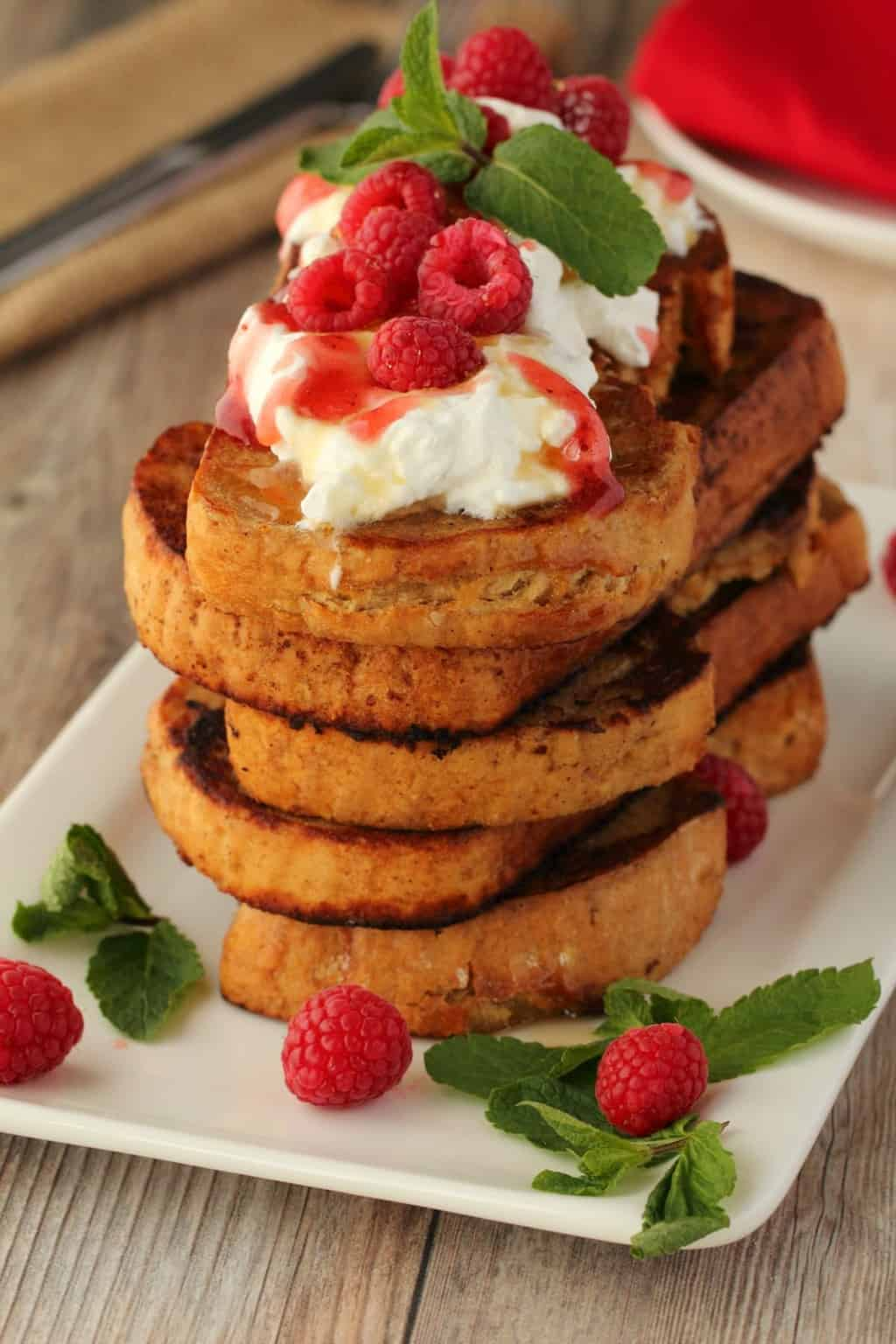 A stack of vegan french toast topped with vegan whipped cream and fresh raspberries.