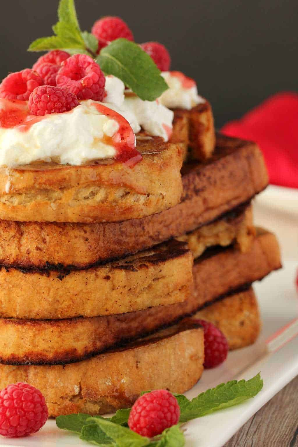 A stack of vegan french toast topped with syrup, vegan whipped cream and fresh raspberries.