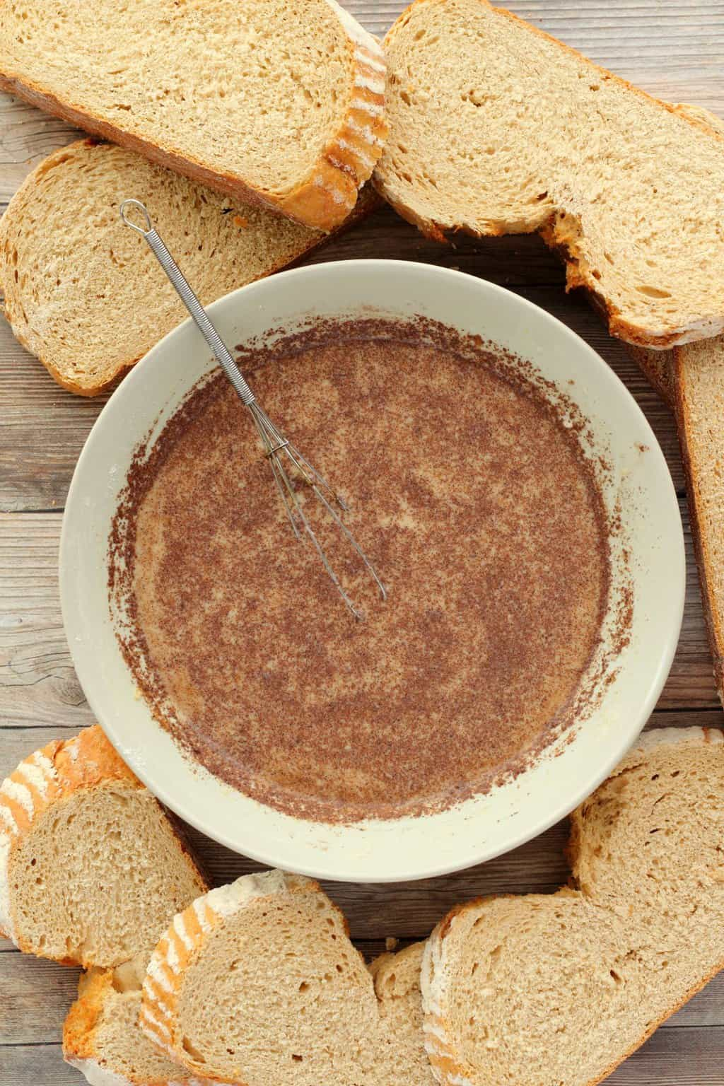 A bowl with the dipping mix for vegan french toast, surrounded by slices of sourdough bread.