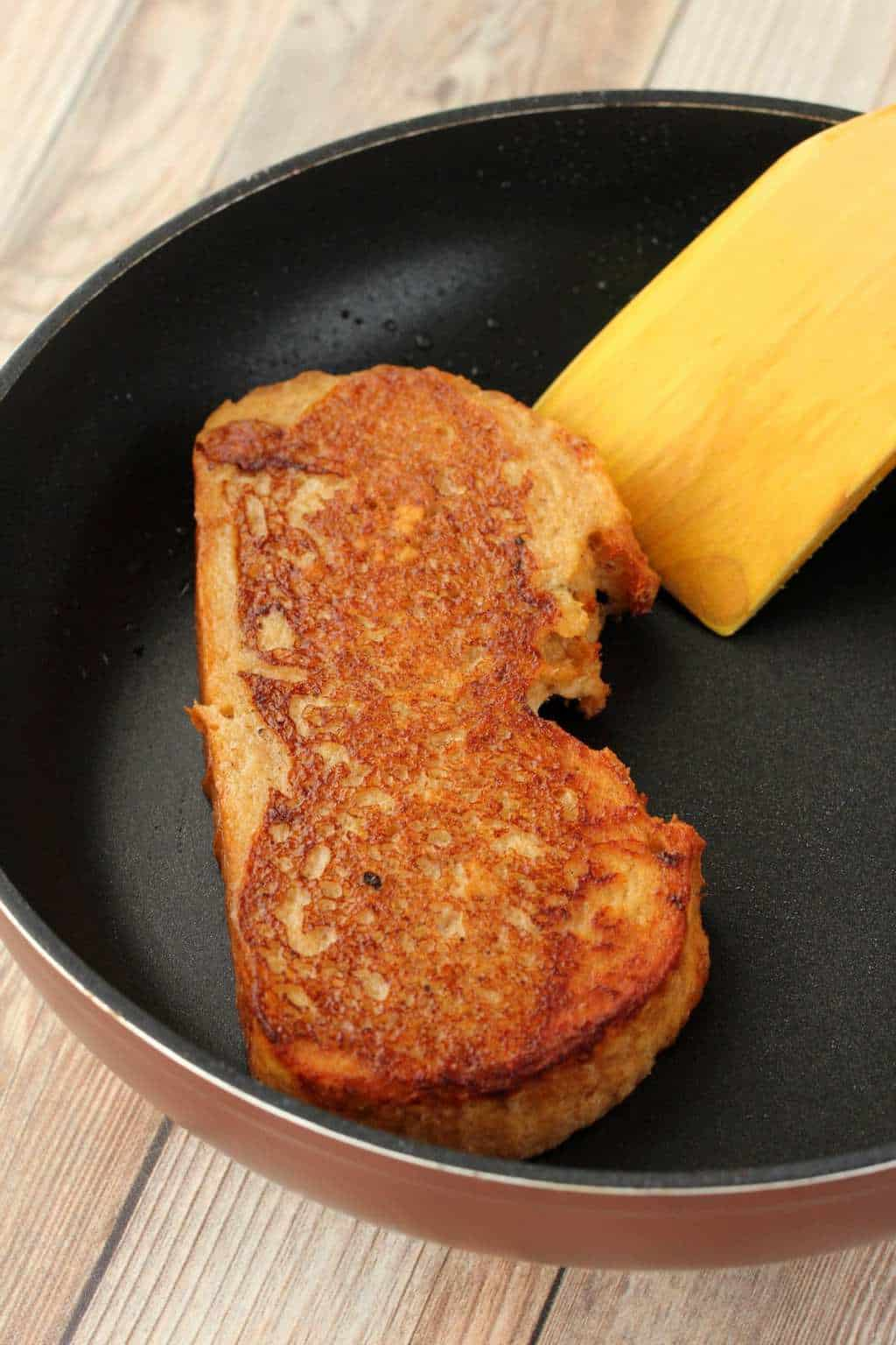 A slice of vegan french toast in a frying pan with a spatula.