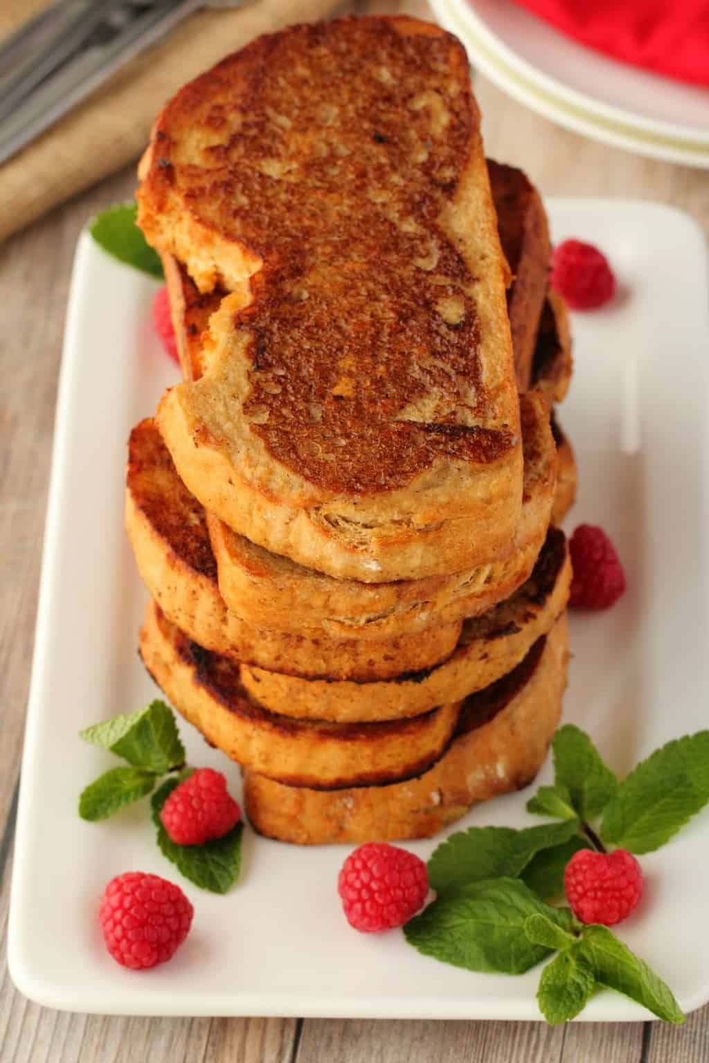 A stack of vegan french toast surrounded by mint leaves and raspberries, on a white plate.