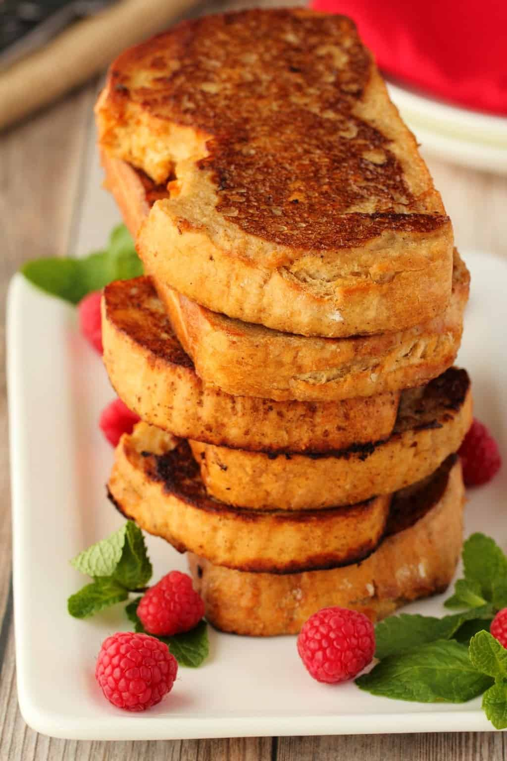 A stack of vegan french toast surrounded by mint leaves and raspberries on a white plate.