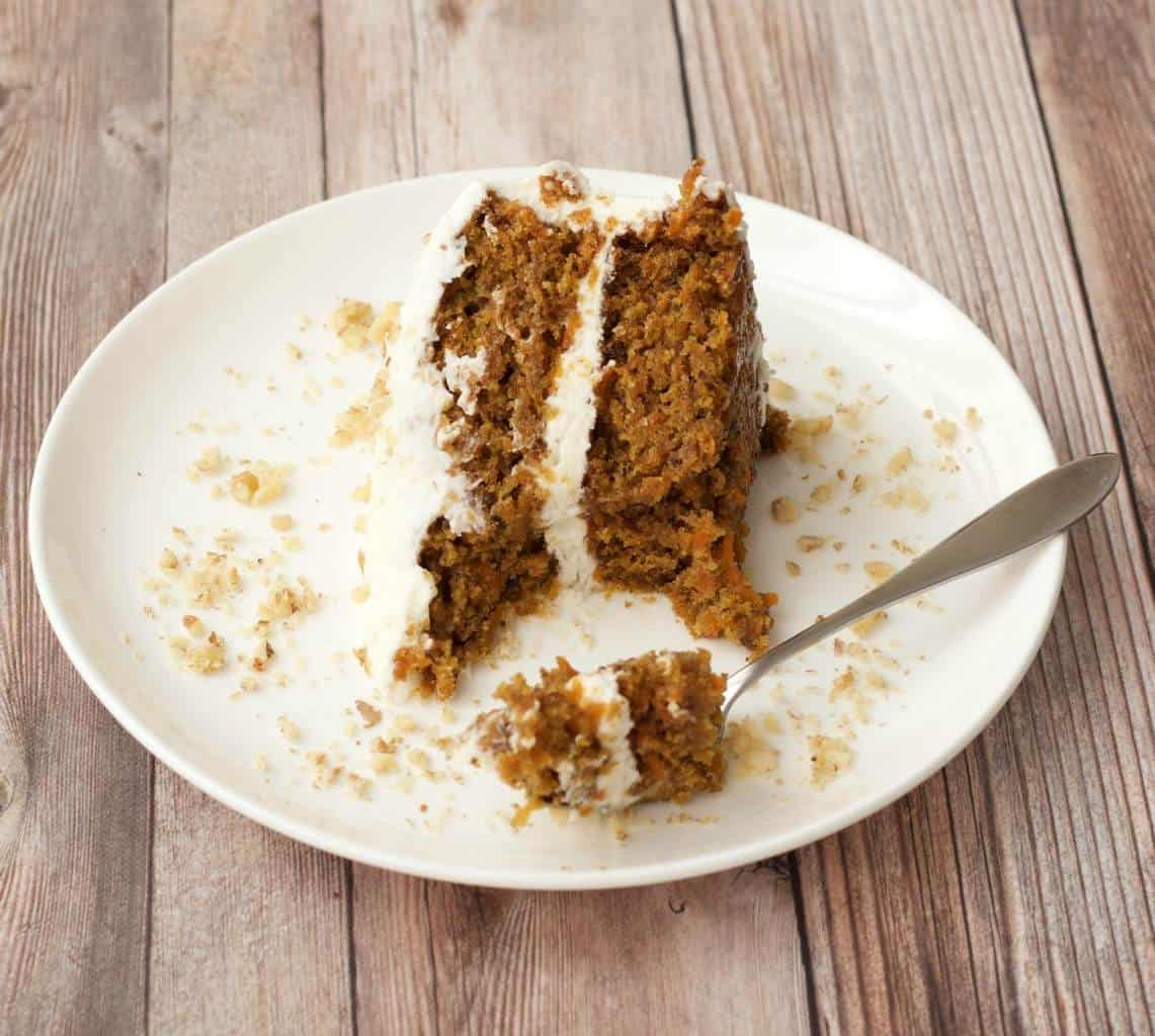 A slice of vegan carrot cake on a white plate with a cake fork.