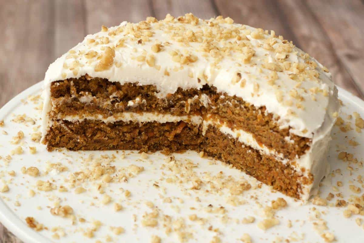Vegan carrot cake on a white cake stand.