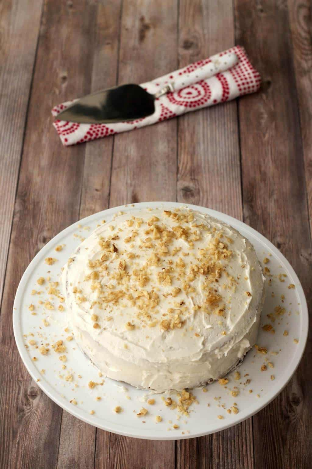 Vegan carrot cake topped with lemon buttercream frosting and crushed walnuts on a white cake stand.