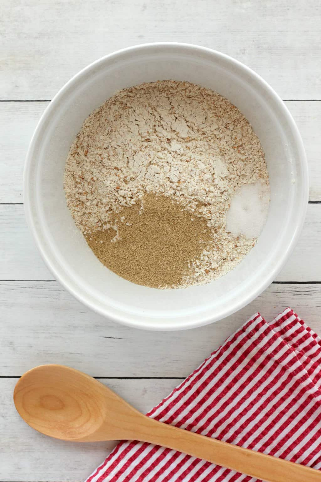 Flour yeast and salt in a mixing bowl, ready to make wholewheat bread.