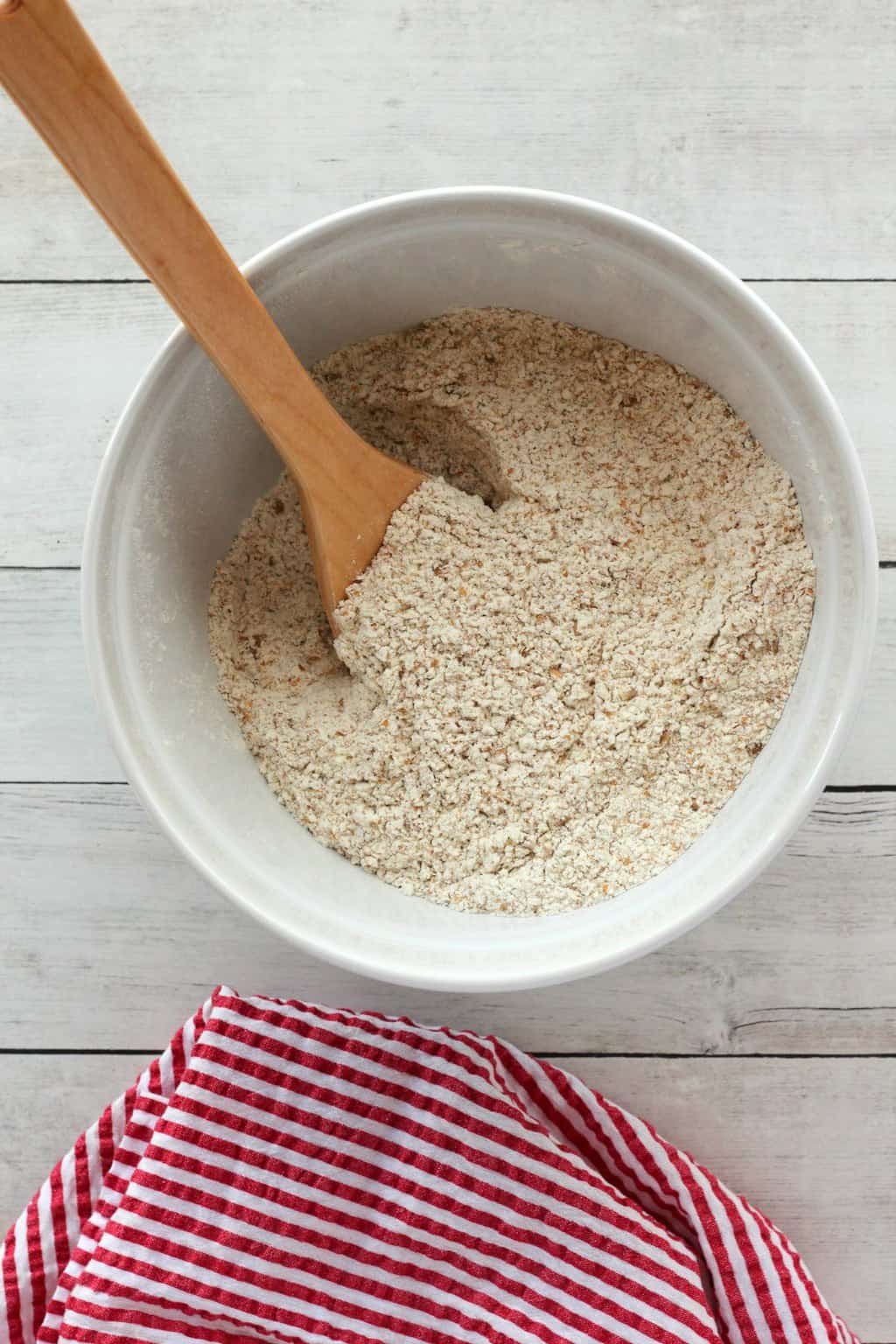 Flour yeast and salt in a mixing bowl with a wooden spoon, ready to make wholewheat bread.