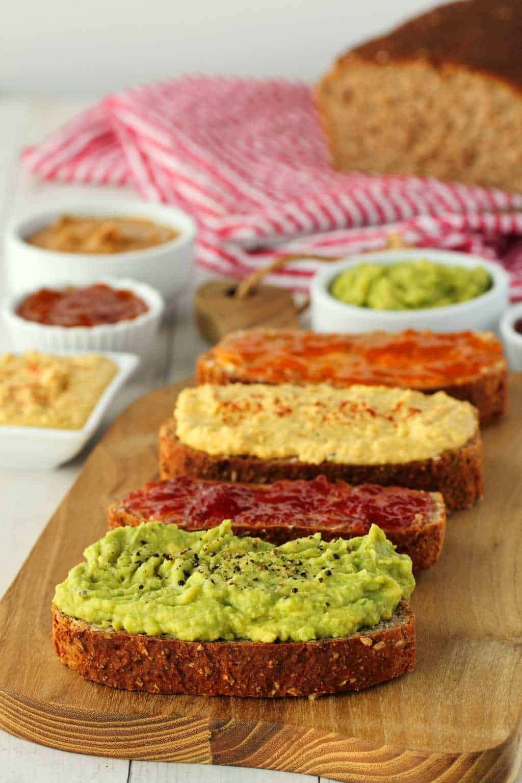 Wholewheat Bread slices topped with avocado, hummus and jams on a wooden board.