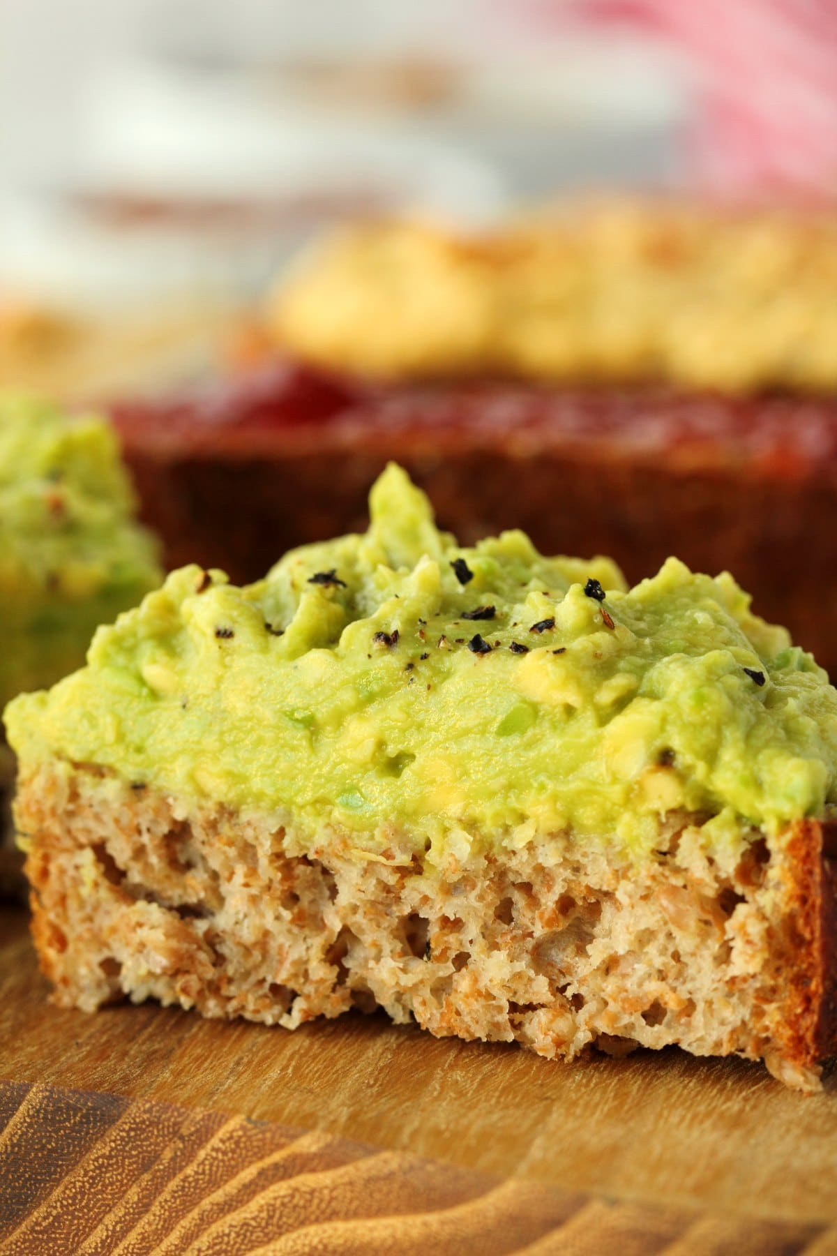 A slice of wholewheat bread topped with avocado and sliced in half.